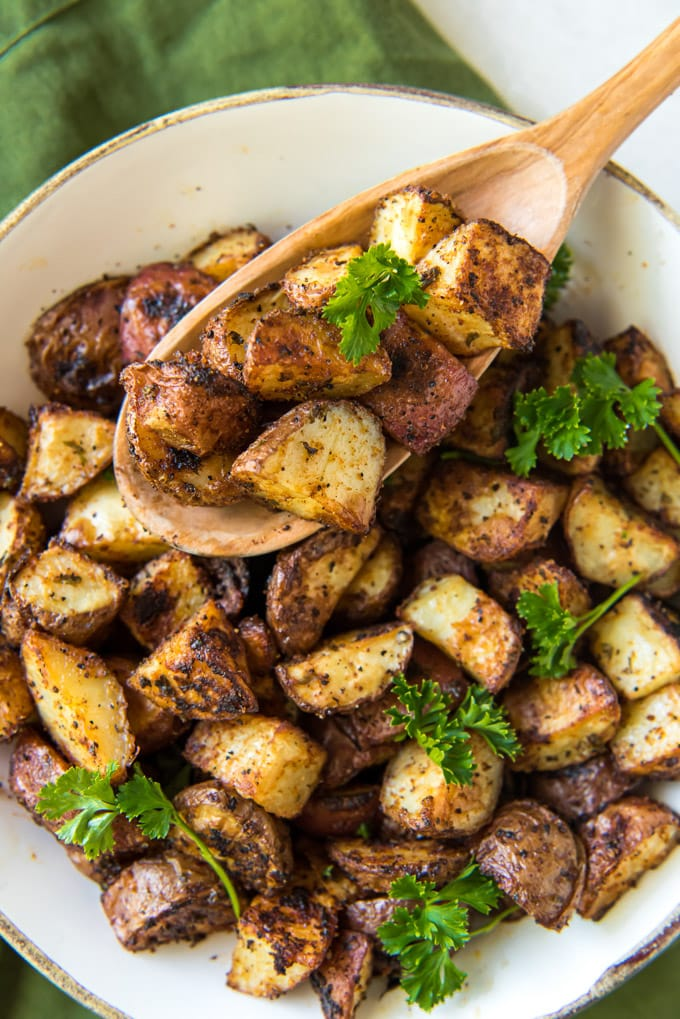 diced red potatoes in a white dish with a wooden spoon and parsley