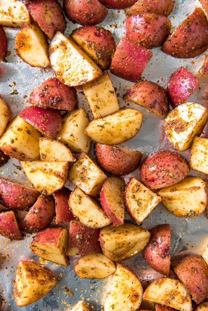 Close up of diced raw red potatoes with olive oil and seasoning