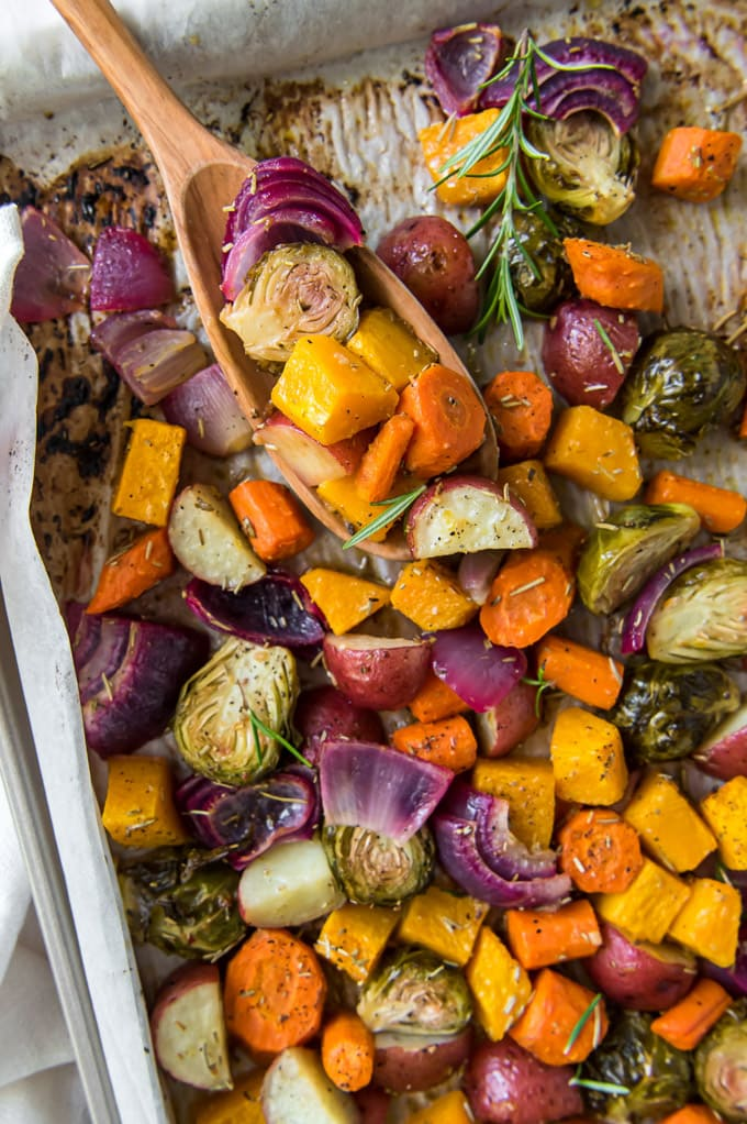 a tray of roasted vegetables with a wooden scoop