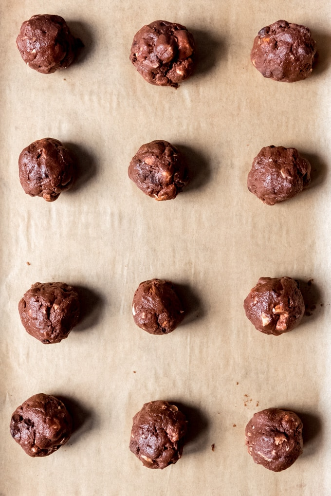 An image of balls of chocolate cookie dough on a baking sheet.