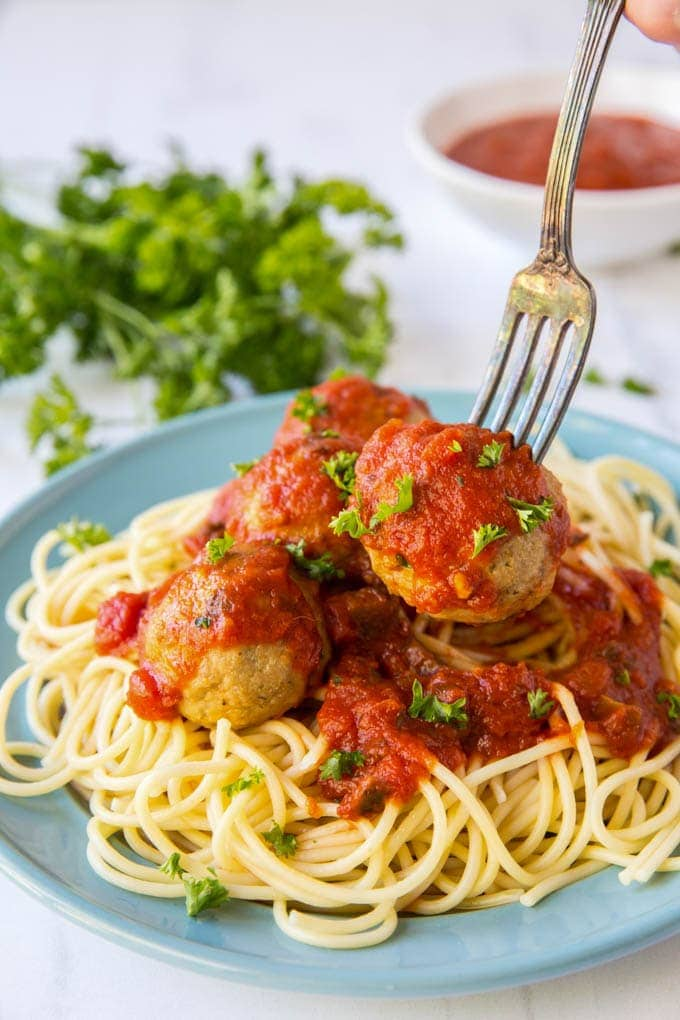 a fork stuck into a meatball, lifting it up off of a plate of spaghetti.