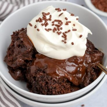 Chocolate Pudding Cake in a white bowl topped with whipped cream and chocolate sprinkles.