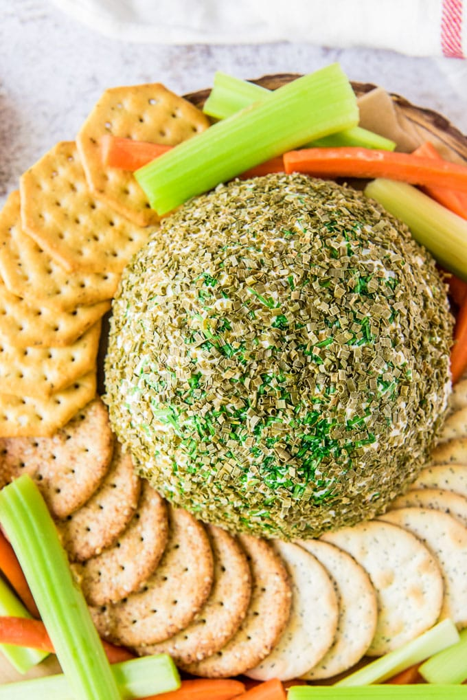 a cheese ball surrounded by crackers and veggie sticks and covered with minced chives.