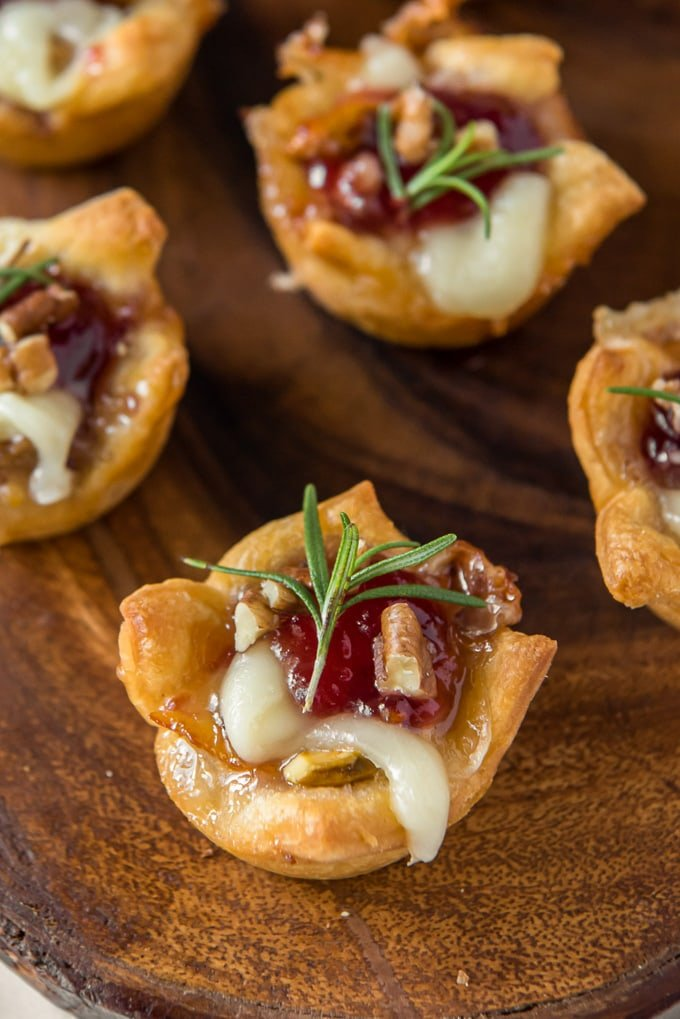 close up of a pastry cup with melted brie and cranberry sauce, topped with rosemary