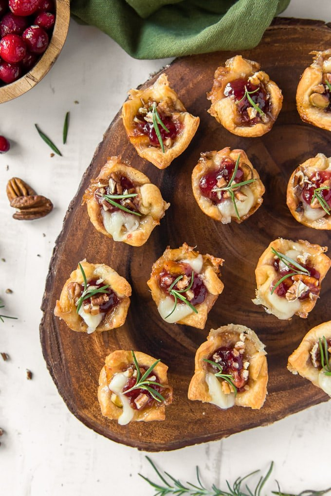 an overhead image of cranberry brie bites on a wooden platter with fresh rosemary