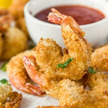 A close up of fried shrimp with dish of cocktail sauce