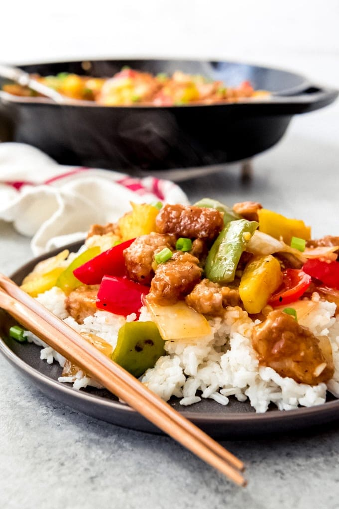 An image of a plate of sweet & sour pork on a bed of white rice.