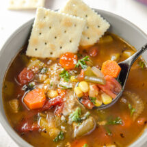 A bowl of vegetable soup with saltine crackers