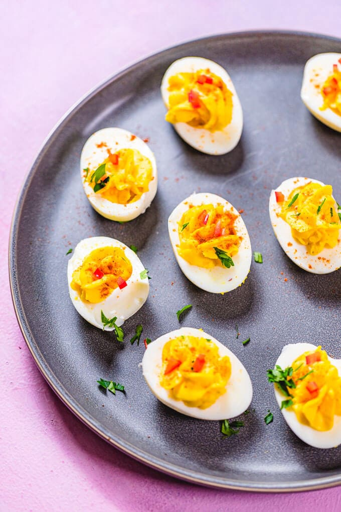 Deviled eggs in grey plate on pink background.