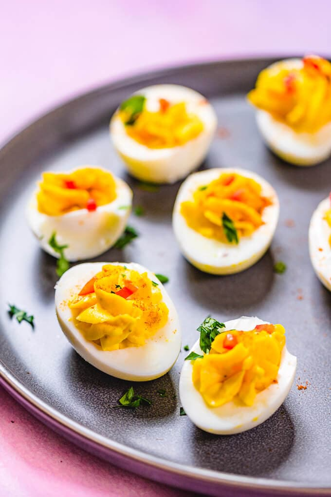 Closeup shot of deviled eggs in grey plate.