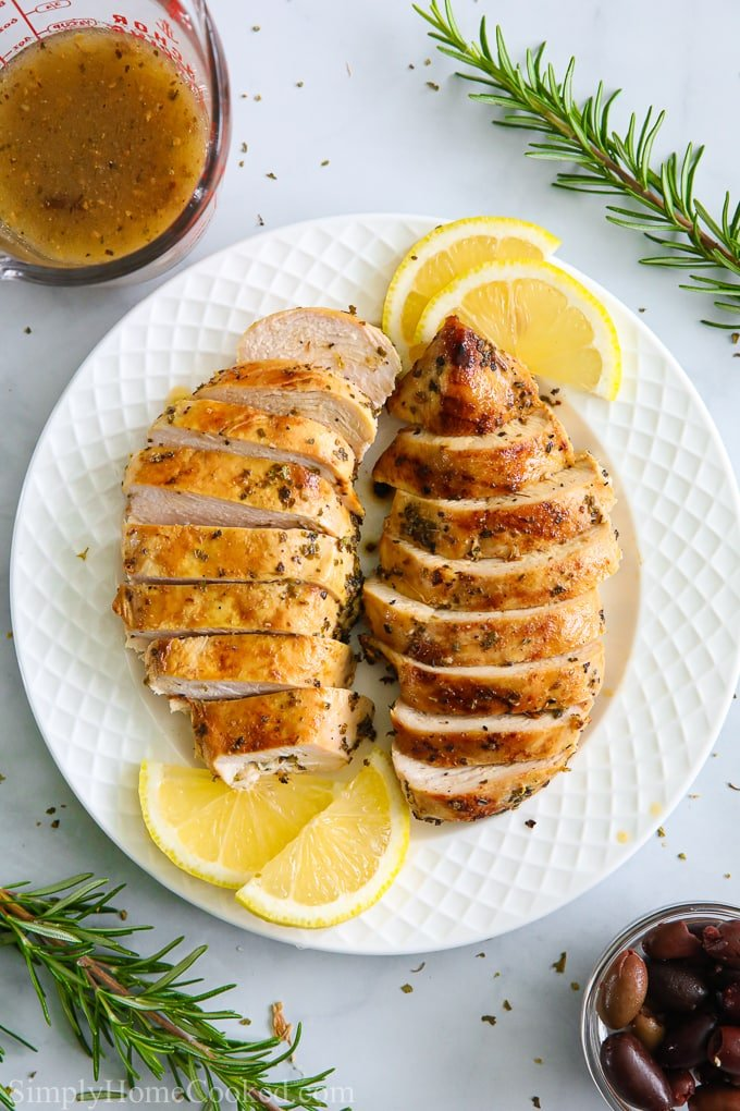 an overhead image of sliced juicy grilled chicken on a white plate with lemons and rosemary around it