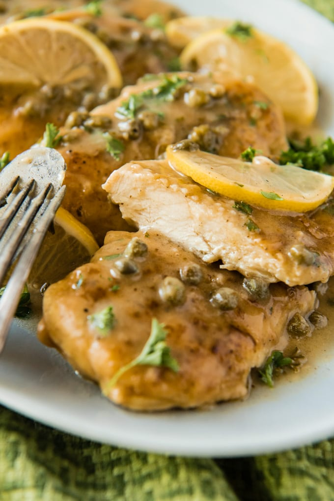 A close up image of a piece of chicken with lemon sauce and capers cut in half