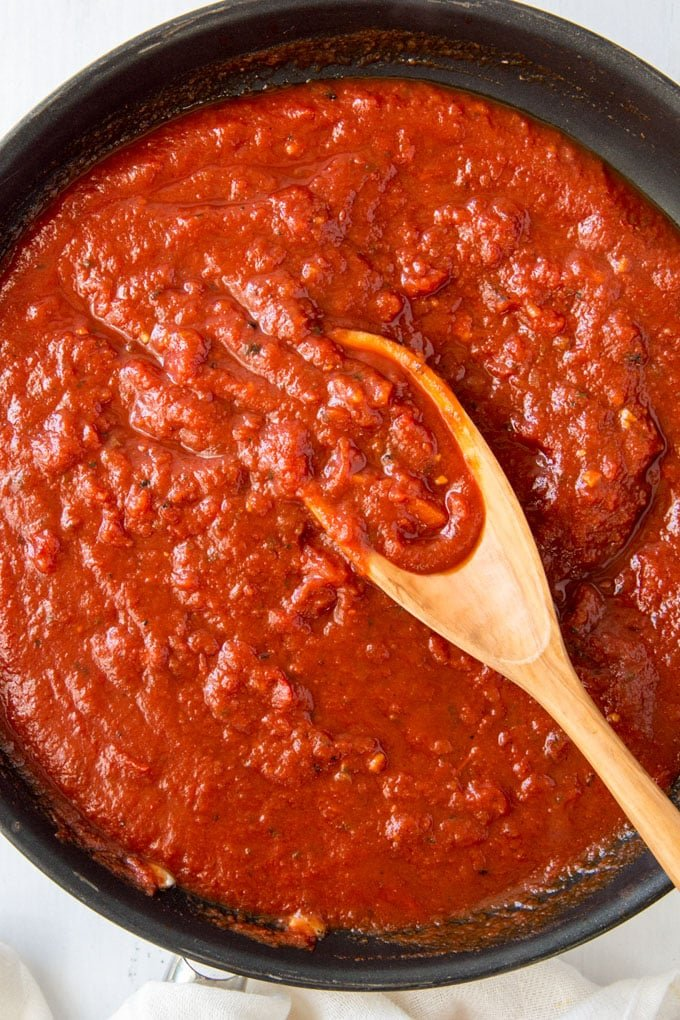 a pan of marinara sauce in a skillet with a wooden spoon