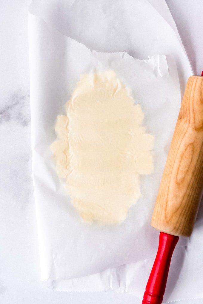 An image of a stick of butter that has been pounded between parchment paper with a rolling pin.
