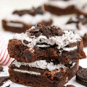 Two Oreo Brownies stacked on top of each other on a piece of parchment paper.
