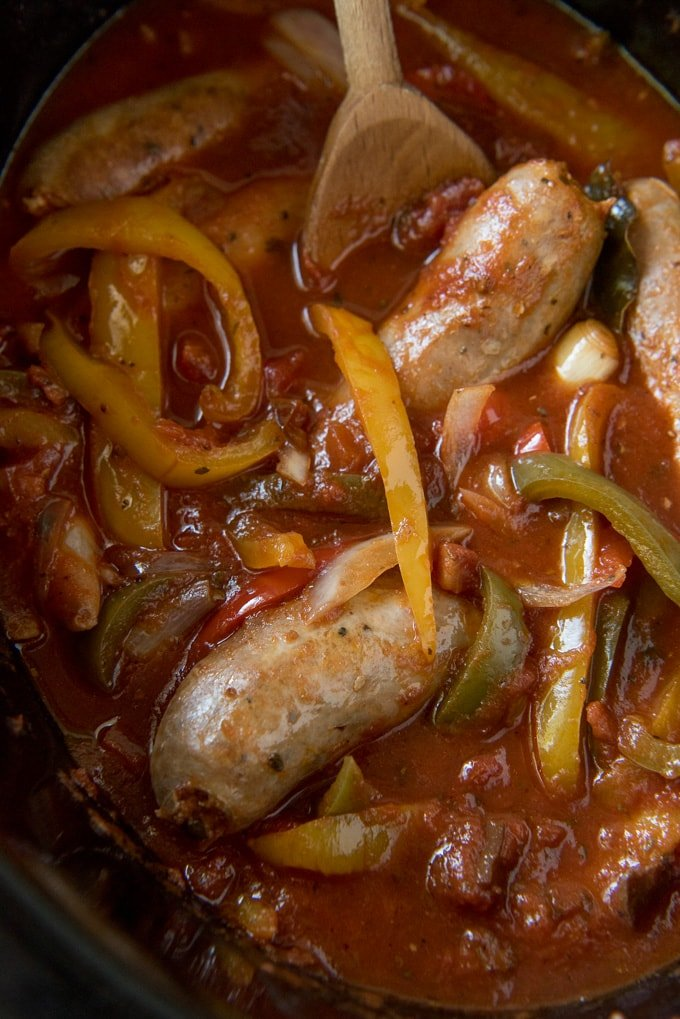 Italian sausage, peppers and onions in marinara sauce in the slow cooker with a wooden spoon.