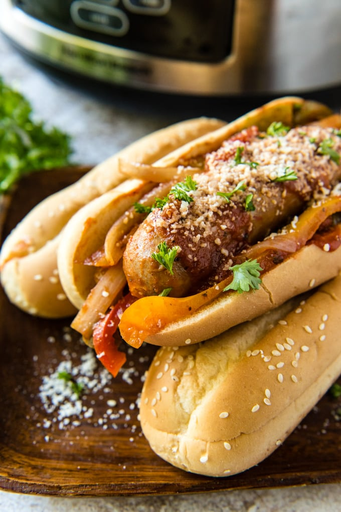 A stack of hoagie rolls with italian sausage adn peppers with a slow cooker in the background.