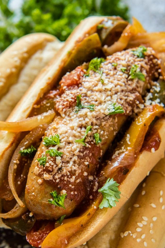 A close up overhead image of italian sausage in a hoagie roll with onions and peppers.
