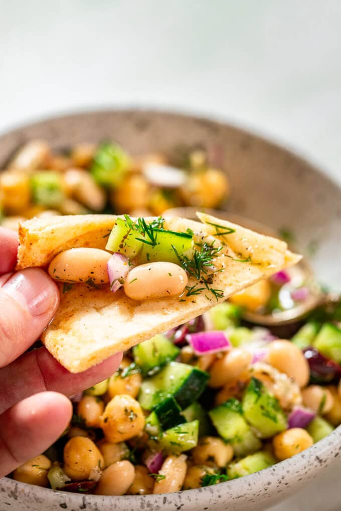 Holding a pita piece with beans, cucumber and dill.