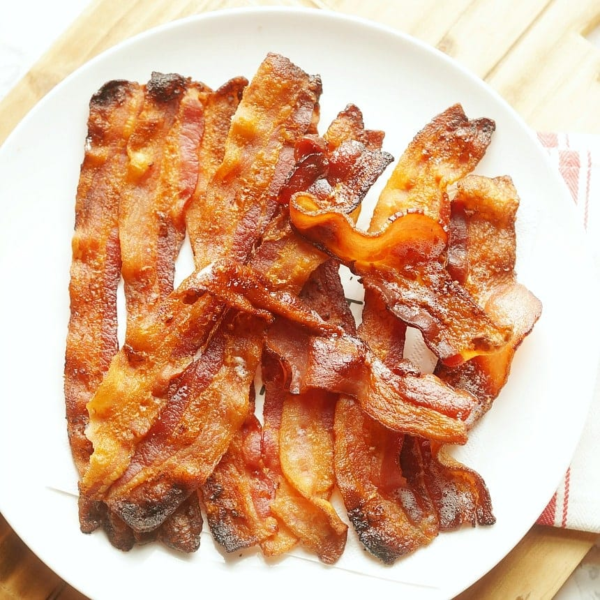 strips of cooked bacon on a white plate.