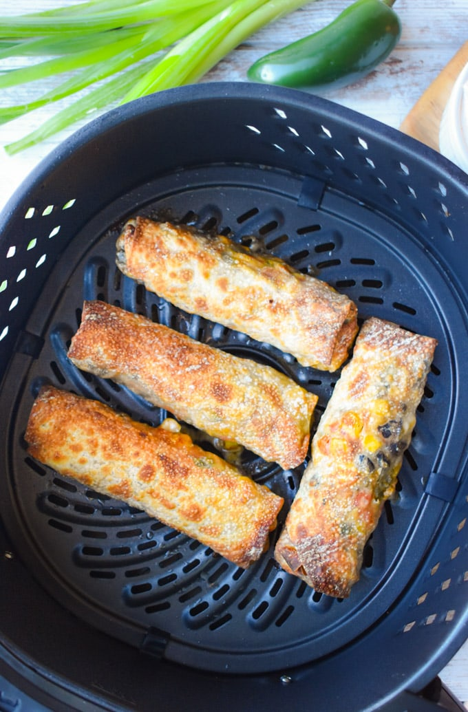Air fryer basket with four egg rolls