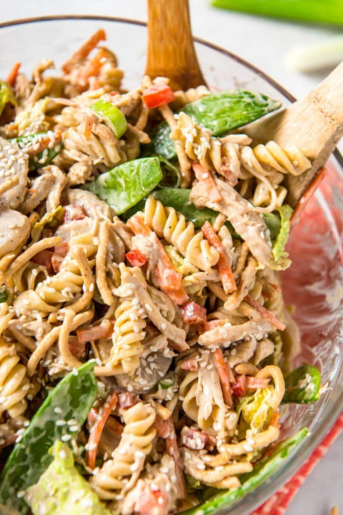 Chinese Chicken Pasta Salad in a large glass bowl with wooden spoons