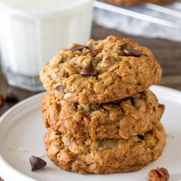 A stack of 3 thick and chewy cowboy cookies.