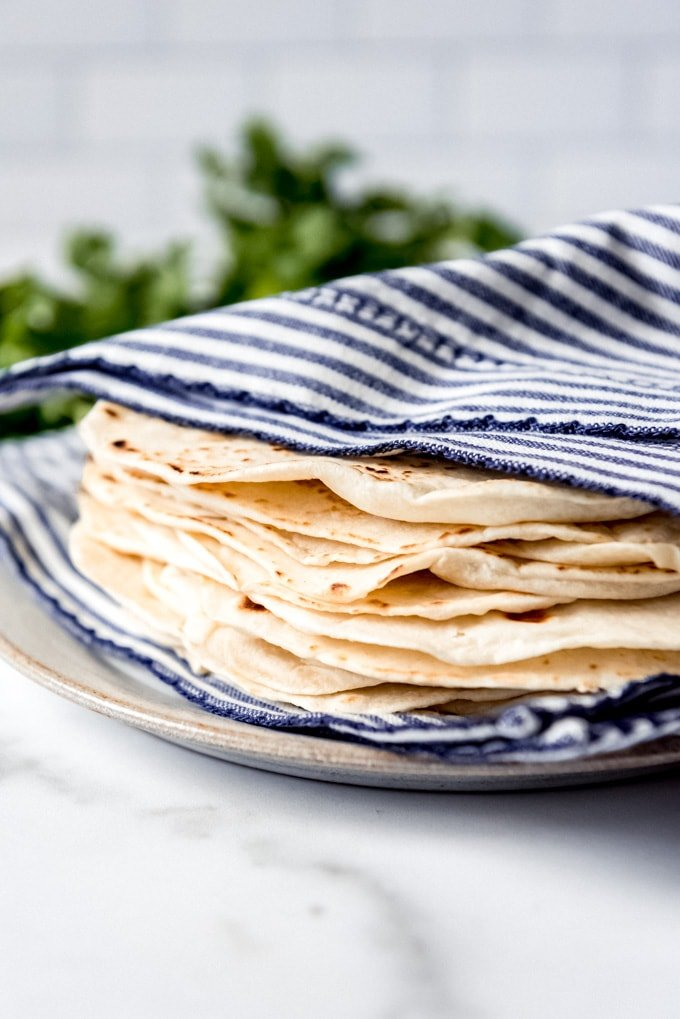 An image of fresh homemade tortillas wrapped in a napkin to stay warm.