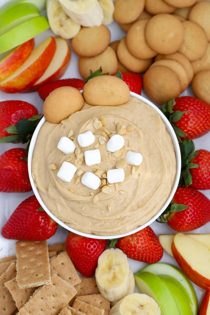 Fluffernutter peanut butter dip topped in a white bowl surrounded by fruit.