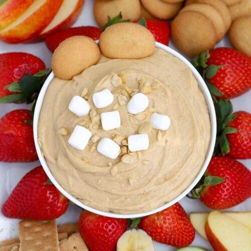 A bowl of Fluffernutter dip with fruit and vanilla wafer cookies