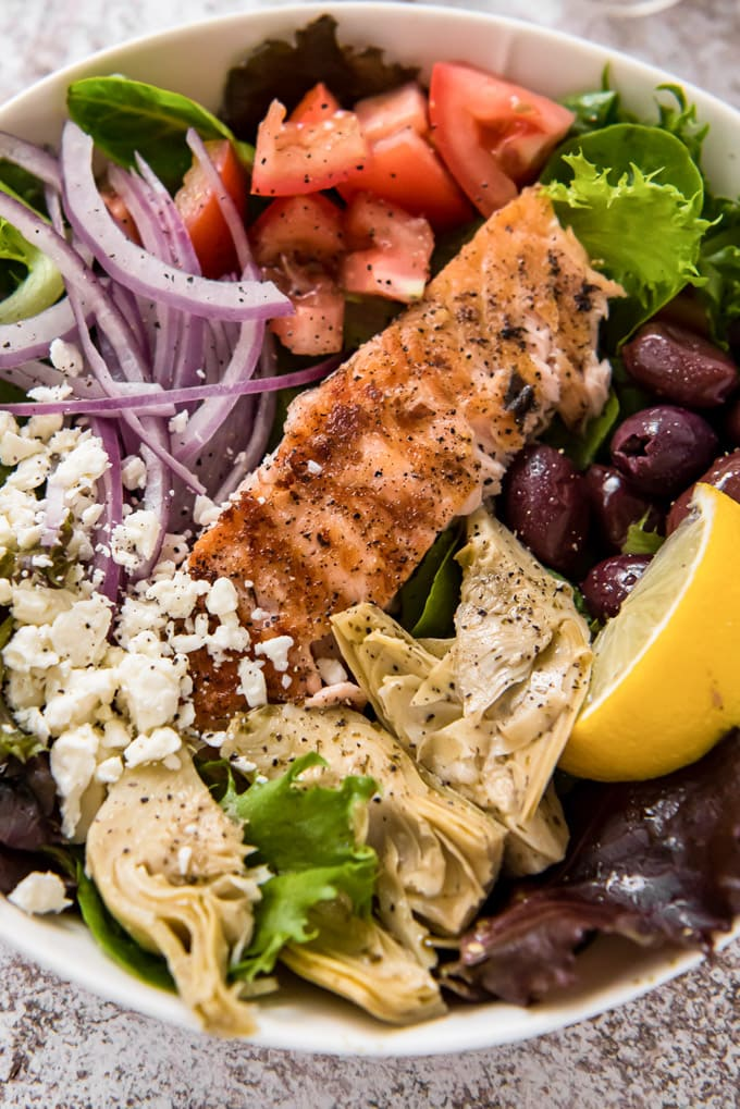 A close up image of a bowl of salad with salmon, artichokes, tomatoes and olives