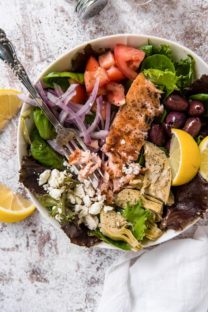 An overhead image of a bowl of grilled salmon salad with olives, tomatoes, feta and artichokes and lemon