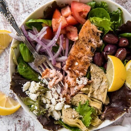 A bowl of salad with salmon, red onions, and olives