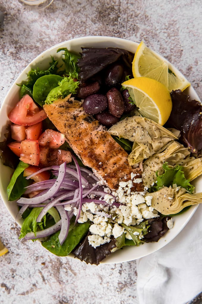 An overhead image of a bowl with lettuce, salmon, artichokes, tomatoes, onions and feta cheese