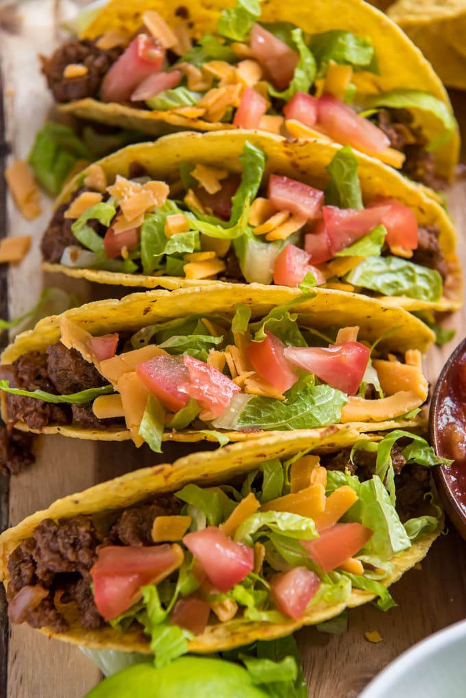 An overhead image of four tacos with ground beef, lettuce, cheese and tomatoes