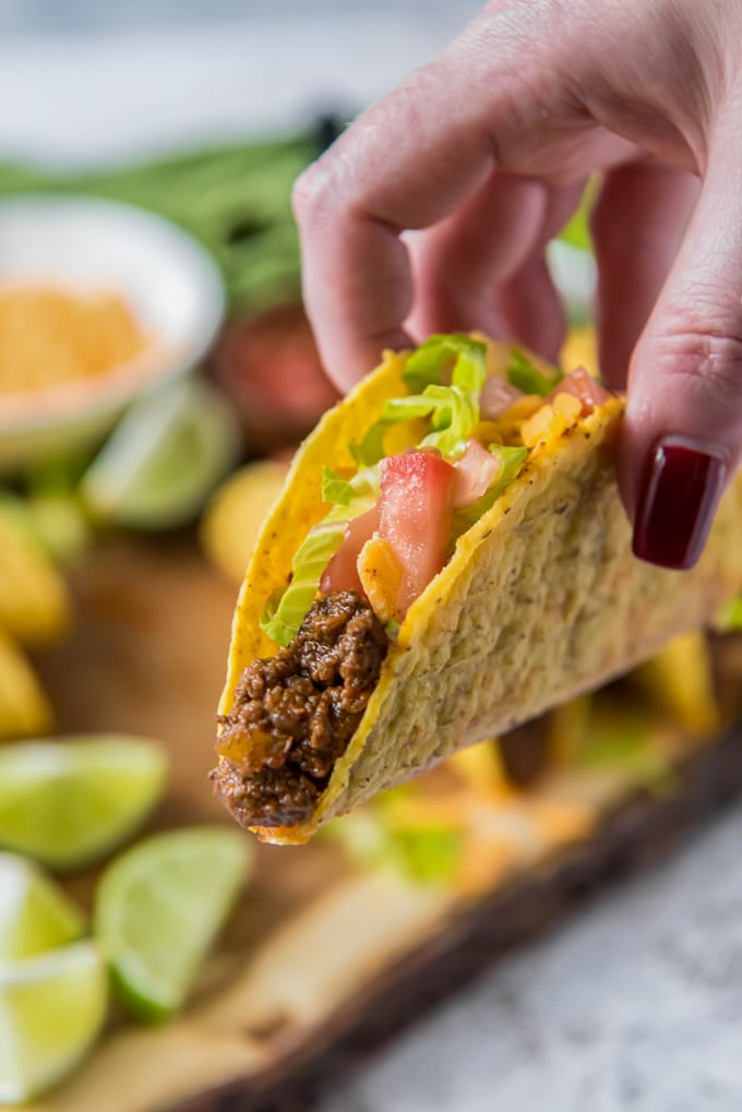 A hand holding a taco filled with ground beef, lettuce, cheese and tomatoes