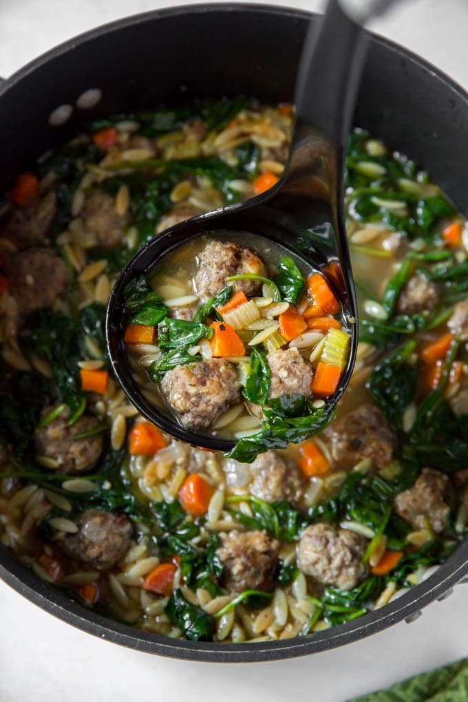 A ladle of Soup with meatballs, spinach, carrots and orzo.