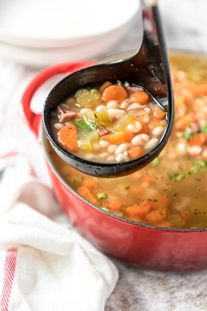 a black ladle with white beans, broth, ham and carrots