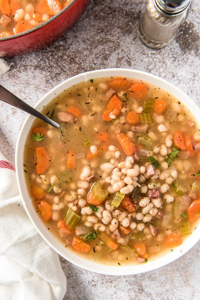 a white bowl filled with beans, carrots and ham soup.