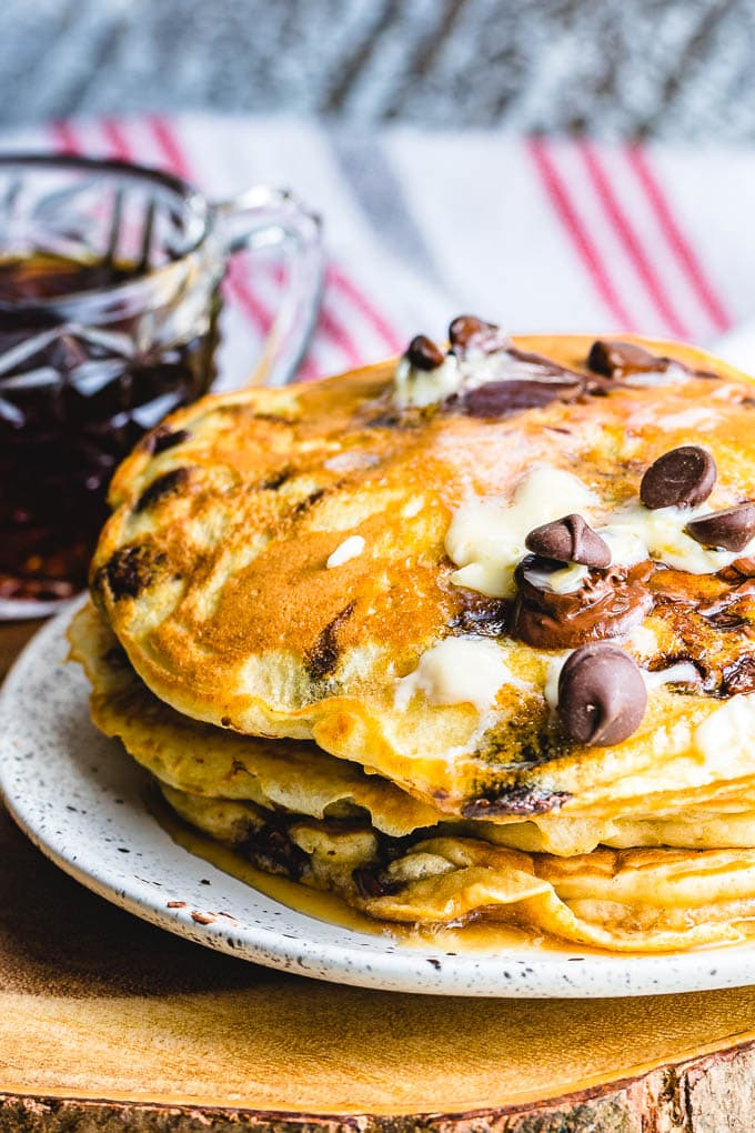 Chocolate chip pancakes in white plate with syrup in background.