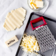 A stick of butter, cheese grater, and grated butter