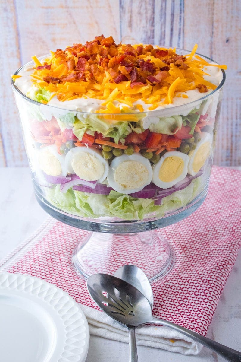layer salad in a trifle bowl with serving spoons and plates
