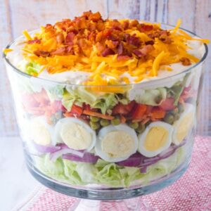 7 Layer Salad is a classic potluck dish great for feeding a crowd. These layers of deliciousness can be made ahead of time for these easiest side dish ever!