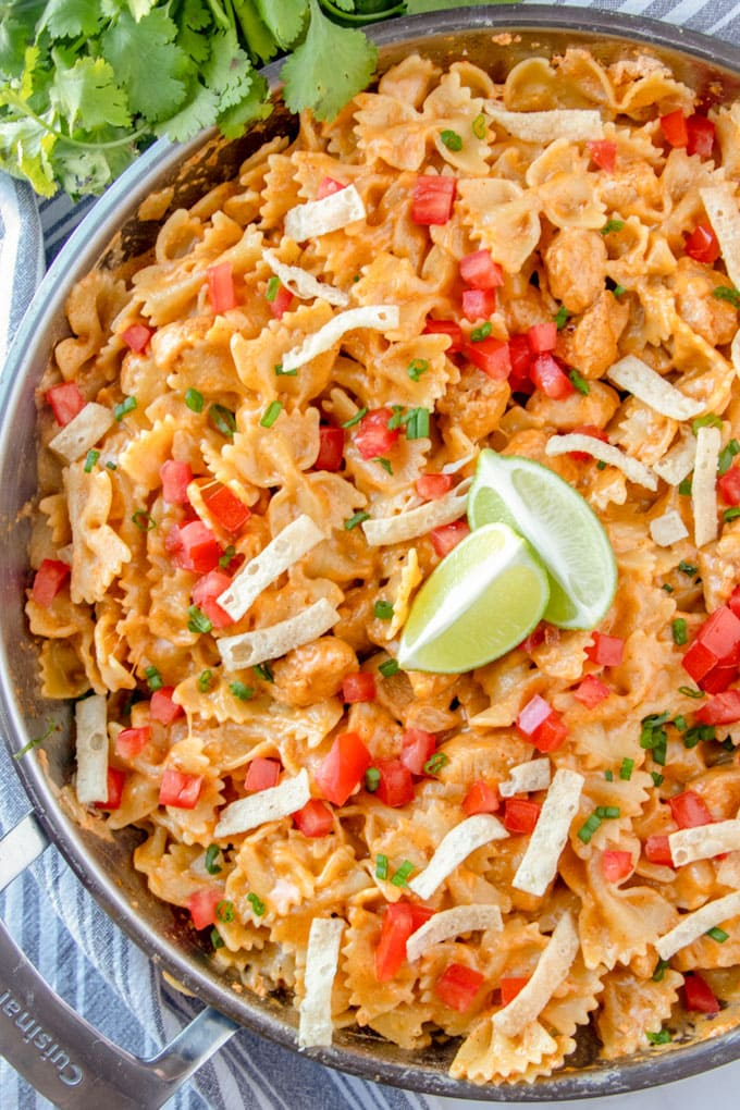an overhead shot of chicken taco pasta with tortilla strips and limes