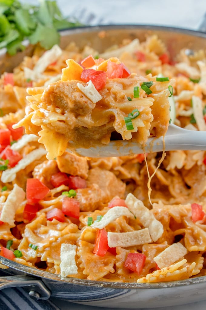 a pot of chicken taco pasta with a serving lifted up by a spoon