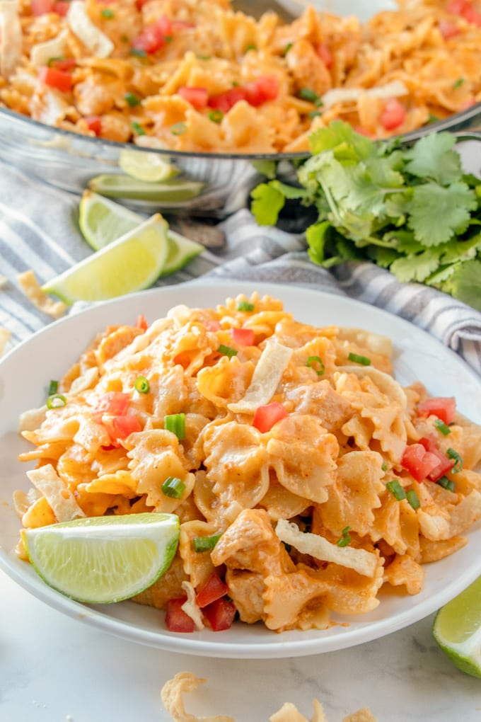 a plate of chicken taco pasta with fresh limes