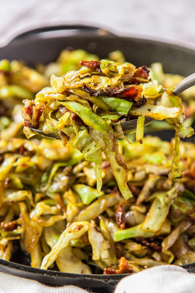 Shredded cabbage and bacon, fried together in a cast iron skillet. A serving is held up by a metal spoon.