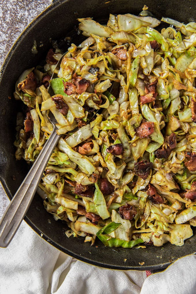 a cast iron skillet with fried cabbage and bacon