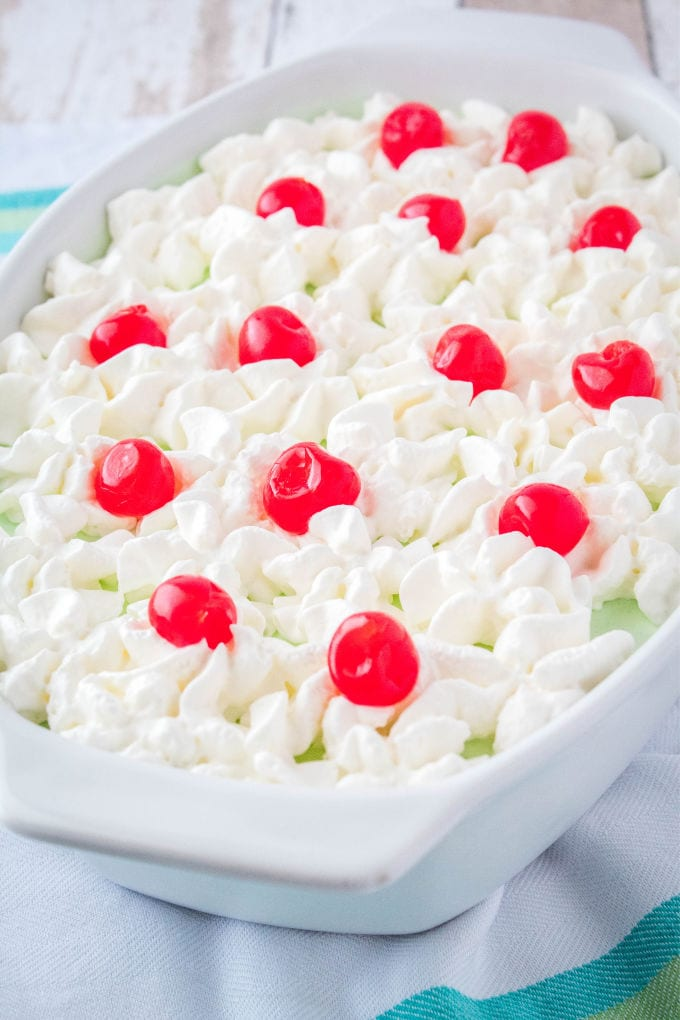 green jello salad topped with whipped cream and cherries