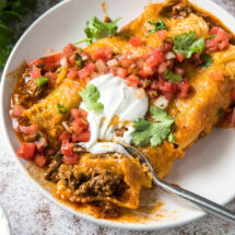 A close up of Beef Enchiladas topped with sour cream, salsa, and cilantro